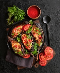 Karniyarik. Stuffed eggplant, eggplant with meat and vegetables, baked with tomato sauce, Turkish cuisine. Top view, close-up