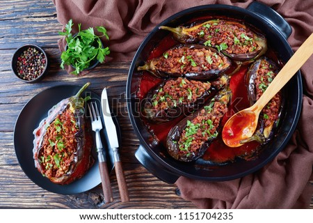 Karniyarik - Stuffed Eggplants, Aubergines with ground beef and vegetables baked with tomato sauce served on a plate with fork and knife, turkish cuisine, horizontal view from above, close-up, flatlay #1151704235