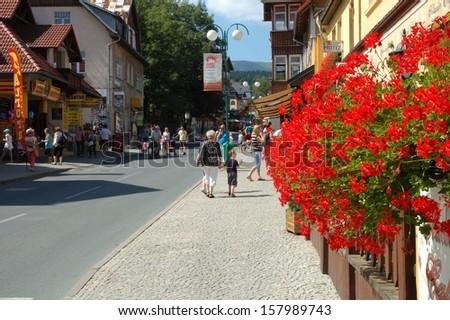 KARPACZ, POLAND - AUGUST 14,2013: Unidentified people and flowers on main street in Karpacz city in Karkonosze mountains Poland