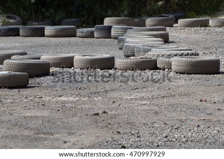 Kart course bounded by old care tires on a gravel area - Detail #470997929