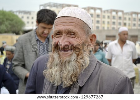 "KASHGAR, CHINA - JUNE 20: senior Uyghur ethnicity man at ""Zhongxiya Shichang"" bazaar, popular animal market in Kashgar it attracts villagers, nomads and tourists on  June 20, 2011 in Kashgar, China"
