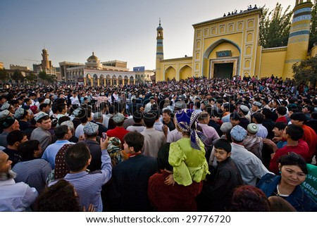 KASHGAR, CHINA - OCT 2 : Crowd watche Uyghur men dance outside Id Kah Mosque after service at the end of Ramadan October 2, 2008 in Kashgar, Xinjiang province western China.