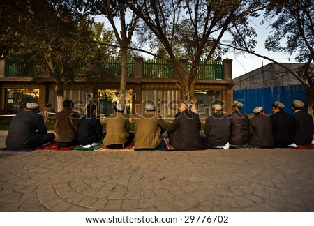 KASHGAR, CHINA - OCT 2: Muslim men sit in a row outside Id Kah Mosque to pray October 2, 2008 in Kashgar,  Xinjiang province western China. The mosque is usually full during Ramadan prayer service.