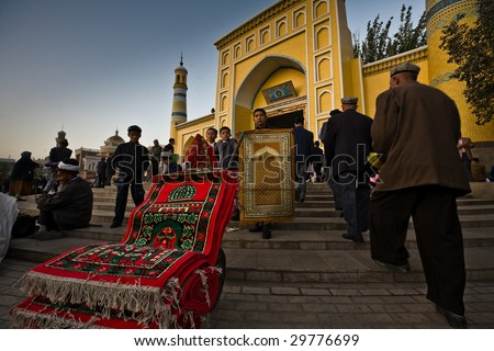 KASHGAR, CHINA- OCT 2: Two Uyghur boys and a man sell colorful prayer carpets on the steps of Id Kah Mosque during Ramadan  month services October 2, 2008 in Kashgar,  Xinjiang province western China.