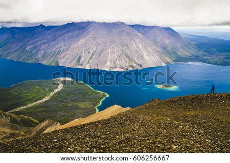 Kathleen Lake in Kluane National Park, Yukon as seen from King's Throne summit. Hiker in the background. Beautiful colorful scenery. Turquoise blue lake, green forests. Wilderness.