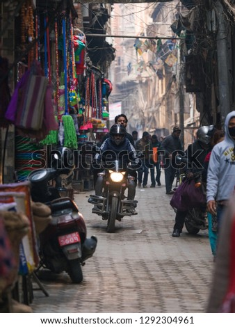 Kathmandu, Nepal - December 9, 2018: People riding bicycle through a narrow lane. #1292304961