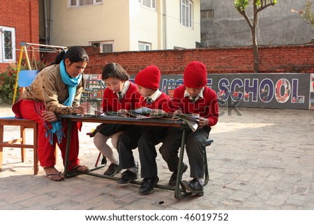 """KATHMANDU, NEPAL - JANUARY 1: A teacher conducts lessons in small primary school """"Happy Home School"""" in poor area of city, January 1, 2009 in Kathmandu, Nepal."""