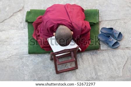 KATHMANDU, NEPAL - NOVEMBER 18: A little Buddhist monk prayers on the street on November 18, 2009 in Kathmandu, Nepal.