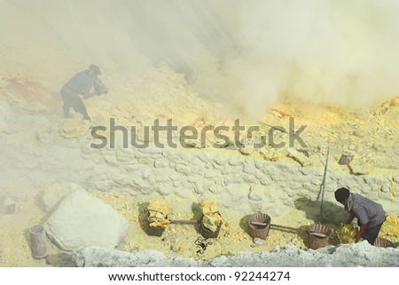 KAWAH IJEN, INDONESIA - SEPT 19 : Unidentified miners harvest raw sulphur from the crater of Kawah Ijen volcano in hazardous working environment with minimal protection on 19 Sept 2010 in Kawah Ijen.