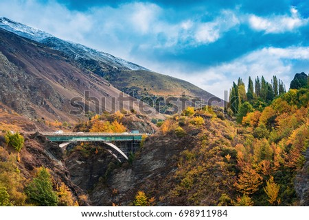 Kawarau bridge near Queenstown, south island, New Zealand in Autumn with changing color leaves tree and hill with cloudy sky. #698911984