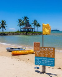 kayak boats at side Beach with caution notice board at beach during sunny clear blue sky day