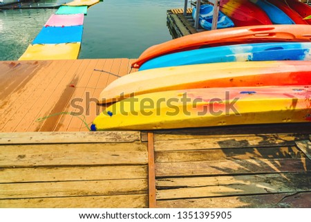 Kayak for rent at Mae Ngad Dam in Chiang Mai, Thailand. Colorful kayaks lay down on the wooden floor. Group of canoes or kayaks t pier. Fiberglass kayaks. Colorful kayaks