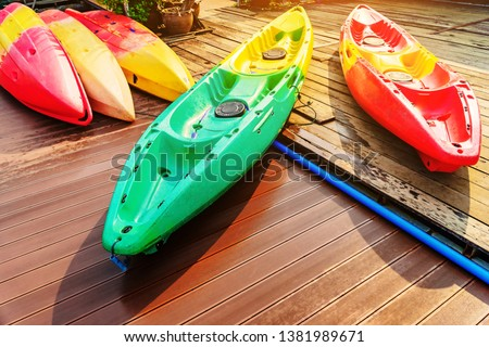 Kayak for rent at Mae Ngad Dam in Chiang Mai, Thailand. Colorful kayaks lay down on the wooden floor. Group of canoes or kayaks t pier. Fiberglass kayaks. Colorful kayaks.