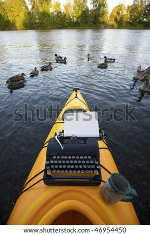 Kayak with a typewriter and a coffee cup on it. - stock photo