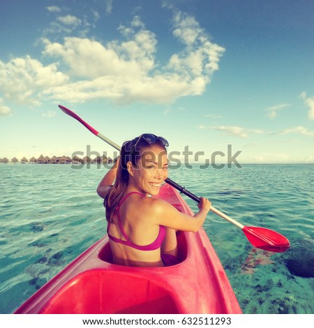 Kayak woman having fun kayaking at tropical beach resort in Tahiti vacation travel. Asian girl enjoying watersport on holidays at sunset. Action camera.