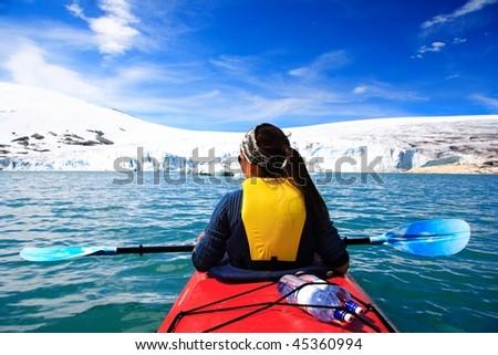 Kayak Woman kayaking at glacier lake at Jostedalsbreen, Norway.