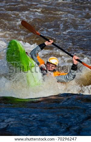 Kayaker doing cartwheel on whitewater