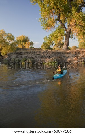 kayaker (fifty five years old male) paddling a blue, plastic, whitewater kayak on a small river in autumn scenery