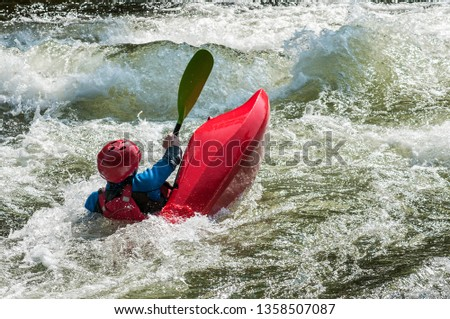 Kayaker in small kayak in whitewater struggling against waves Gull river Ontario Canada