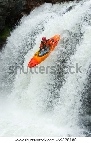 Kayaker jumping from a waterfall