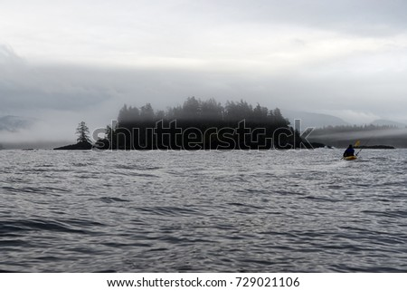 Kayaker paddling near small woody island at Foggy Bay, Alaska, USA #729021106