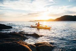 Kayaker paddling the kayak at sunset sea. Kayaking, canoe, paddling