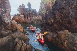 kayaking, adventure travel, group of people on kayaks between cliffs