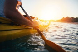 Kayaking. Close up of man holding kayak paddle at sunset sea
