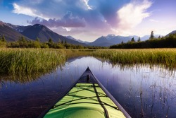Kayaking in a beautiful lake surrounded by the Canadian Mountain Landscape. Colorful Sunset Sky Art Render. Vermilion Lakes, Banff, Alberta, Canada.
