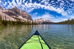Kayaking in a glacier lake during a vibrant sunny summer morning. Blue Sky Art Render. Taken in Bow Lake, Banff National Park, Alberta, Canada.