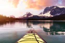 Kayaking in a glacier lake during a vibrant sunny summer morning. Sunrise Sky Art Render. Taken in Bow Lake, Banff National Park, Alberta, Canada.