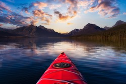 Kayaking in Lake McDonald with American Rocky Mountains in the background. Colorful Sunrise Sky Art Render. Taken in Glacier National Park, Montana, USA.
