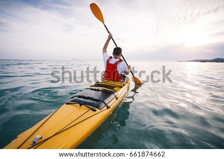 Kayaking. Rear view of man kayaker paddling sea kayak