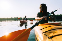Kayaking together. Beautiful young couple kayaking on lake together and smiling