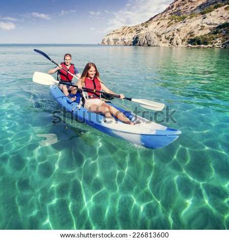 Kayaking. Young couple is sailing on a sea kayak. Sports and recreation on the water.