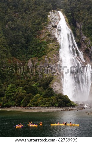Kayaks by waterfall in beautiful Milford Sound - stock photo