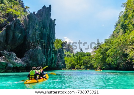 Kayaks in the big lagoon with turquoise clean water, tropical forest , rocks,,  El Nido, Palawan, Philippines
