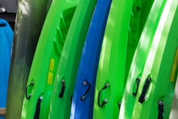 Kayaks lined up and ready for use.  Kayak rentals for paddling down the river and enjoying a relaxing day on the water.  Recreational boating.  Colorful boats.