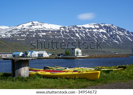 Kayaks Lining The Shore At Seydisfjordur In Iceland'S East Fjords