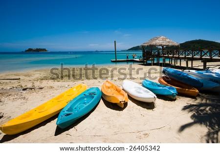 Kayaks on a tropical beach - stock photo