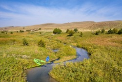kayaks on the shore of a stream meandering in Nebraska Sandhills - North Fork of Dismal RIver near Dismal RIver Golf Club, early fall aerial view