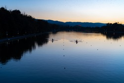 Kayaks racing in canal water reservoir for rowing sport practice on sunset vibrant background in Plovdiv, Bulgaria