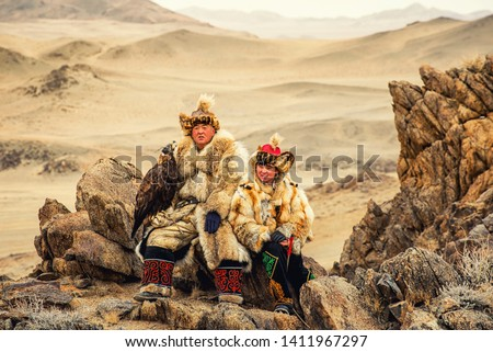 Kazakh Eagle Hunter in traditionally trained golden eagles riding horse in a desert mountain Golden Eagle Festival. Olgei,Western Mongolia.