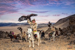 Kazakh Eagle Hunter in traditionally trained golden eagles riding horse in a desert mountain. Olgei,Western Mongolia.