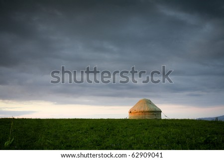 Kazakh yurt stands on a green meadow under cloudy sky