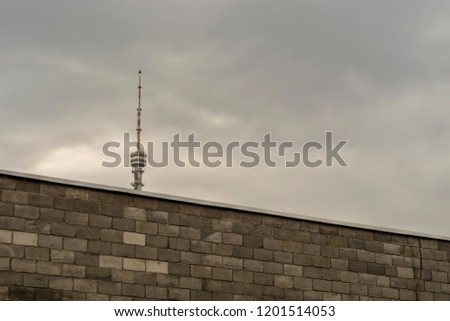 Kazakhstan, Almaty - September 10, 2018 TV Tower on Kok-Tobe is Half Hidden by a Stone Fence in the Foreground. #1201514053