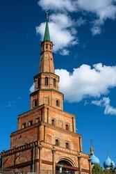 Kazan Kremlin, Tatarstan, Russia. Leaning Suyumbike Tower is famous tourist attraction of Kazan. Vertical view of monument, historical landmark on blue sky background in Kazan city center in summer.