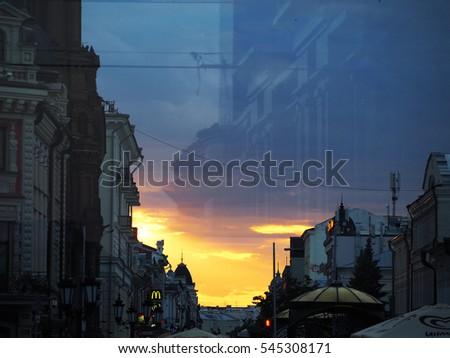 KAZAN, REPUBLIC TATARSTAN, RUSSIA - JUNE, 2016: Evening Kazan, sunset. Bauman Street, the view through the glass of the bus stop at the Square of Tukai #545308171