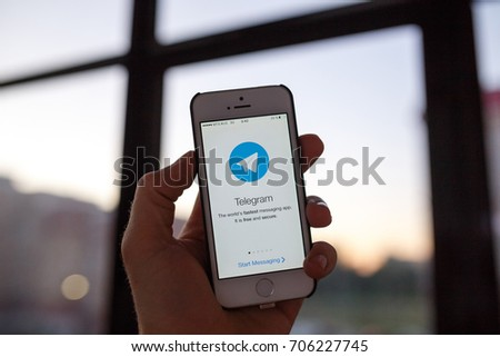Kazan Russia 07.08.2016: iphone 5s with telegram messenger logo on screen, window on background. Illustrative editorial