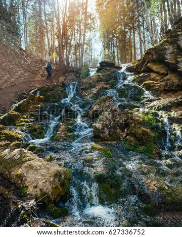 Kazu grava waterfalls with a hiker going up the waterfall and lightened by sun beams. Foto stock ©
